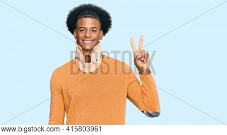 African american man with afro hair wearing cervical neck collar showing and pointing up with fingers number two while smiling confident and happy.