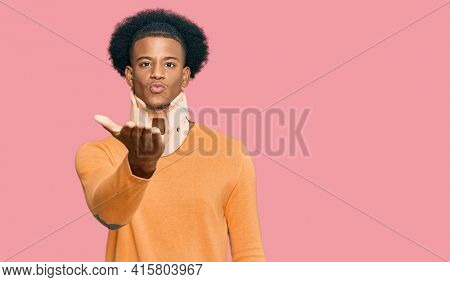 African american man with afro hair wearing cervical neck collar looking at the camera blowing a kiss with hand on air being lovely and sexy. love expression.