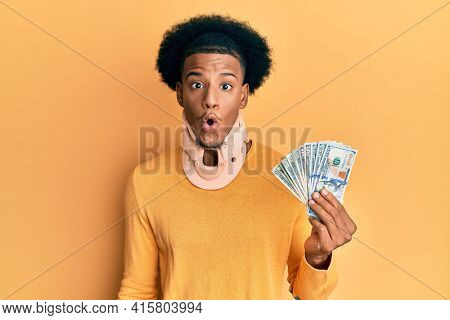 African american man with afro hair wearing cervical neck collar and holding money from insurance scared and amazed with open mouth for surprise, disbelief face