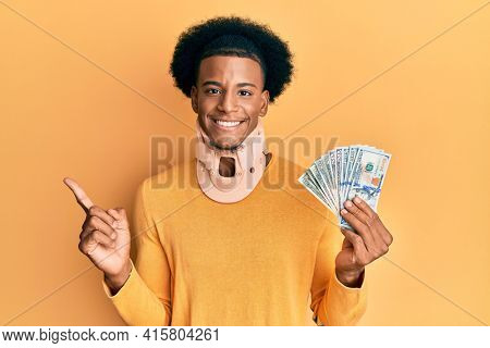 African american man with afro hair wearing cervical neck collar and holding money from insurance smiling happy pointing with hand and finger to the side