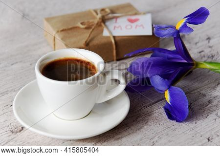 White Cup Of Coffee, Gift Box With Message For Mom And Iris Flower On Gray Wood Table. Mother's Day