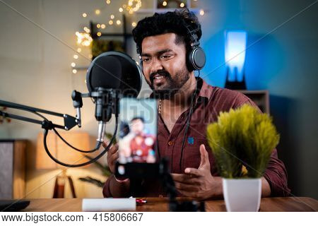 Young Social Media Influencer Recording His Podcast On Mobile Phone - Concept Of Vlogging, Content C