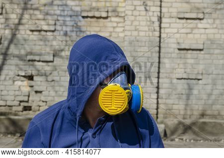 Portrait Of An Adult Unrecognizable Man Wearing A Respirator And Hood On Against A Brick Wall. A Mid
