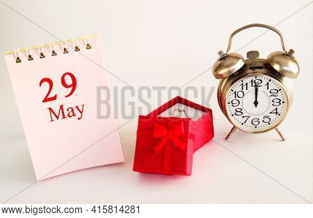 Calendar Date On Light Background With Red Gift Box With Ring And Alarm Clock With Copy Space. May 2