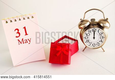 Calendar Date On Light Background With Red Gift Box With Ring And Alarm Clock With Copy Space. May 3