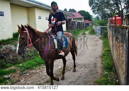 Indonesian People Riding Horse On Street In Small Alley Of Village Go To Landmarks Place For Tour Se