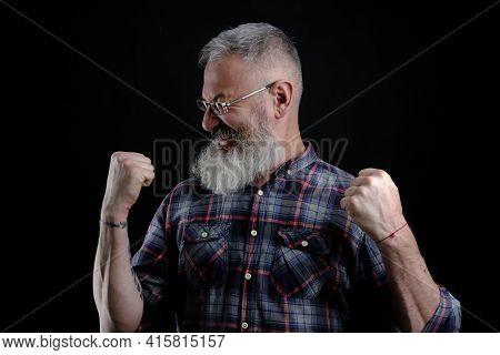 Portrait Of Happy Joyful And Emotive Bearded Mature European Guy, Raising Fists High And Yelling, Tr