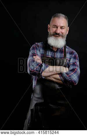 Portrait Of Handsome Mature Bearded Man Dressed Leather Apron Isolated On Black Background, Caucasia