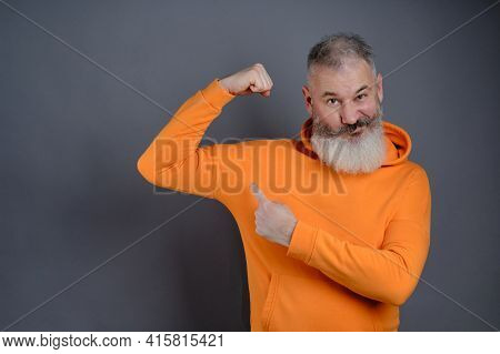 Senior Bearded Man Dressed Orange Hoodie Shows Muscles After Practising Over Gray Studio Background,
