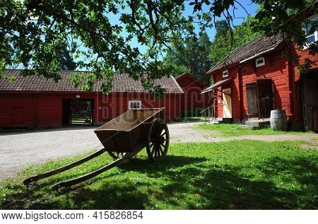 Vasteras, Sweden - Jul 03, 2019: Old wooden cart on big wheels on green grass in yard surrounded by Swedish traditional red houses in Vallby open-air Museum. Summer sunny day
