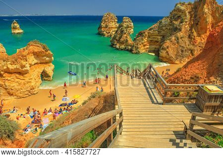 Lagos, Portugal - August 21, 2017: Wooden Walkway Staircase To Scenic Praia Do Camilo With Clear Wat