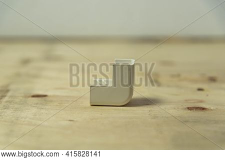 Electrical Connector Type Elbow 90 Degrees On Wooden Background. Electric Material. Plugs And Connec