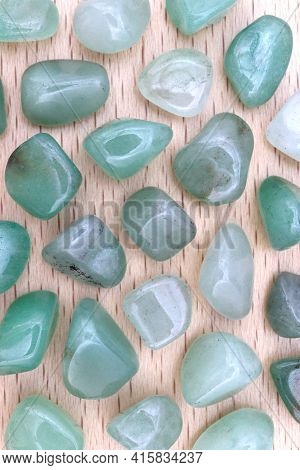 Green Aventurine Rare Jewel On Brown Varnished Wood Texture. Sparse Mineral Pebbles Background.