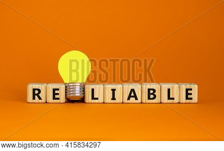 Reliable Symbol. Wooden Cubes With The Word Reliable. Yellow Light Bulb. Beautiful Orange Background