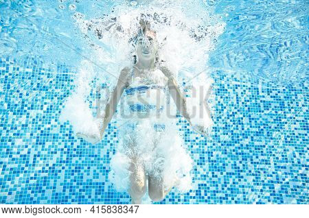 Child Swims In Swimming Pool Underwater, Happy Active Girl Jumps, Dives And Has Fun Under Water, Kid