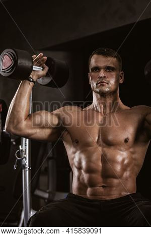 Fitness in gym, sport and healthy lifestyle concept. Handsome athletic man with naked torso making exercises. Bodybuilder male model training muscles lifting large dumbbells up