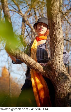 Mature Woman In Interesting Dress And Long Orange Scarf In Autumn Park And Trees With Yellow Leaves