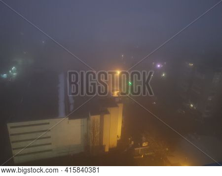 Mysterious Night City In Mist. Aerial View Cityscape While Foggy Weather. Horror Thriller Concept