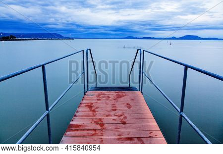 tranquil lake and wooden plank