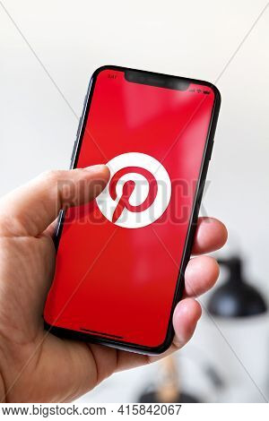 Paris - France - March 23, 2021 : Hand Holding Iphone Smartphone With Pinterest Logo