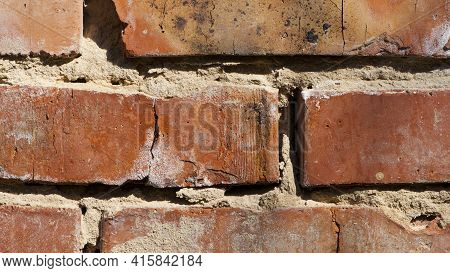 Broken Old Brick Wall. Part Of An Old Red Brick Wall With Cement. Close-up Old Texture, Worn Wall Of