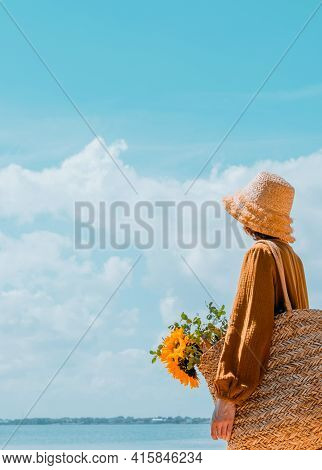 From Behind Young Woman Resting On The Beach. Girl In Straw Hat  Enjoying The Beautiful View. Photos
