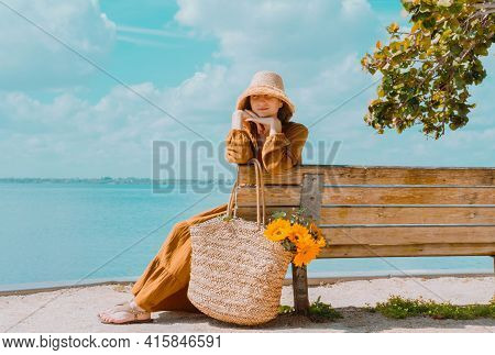 Young Woman In Beautiful Dress Sits On Bench By The Lake And Enjoys The View Rest On A Sunny Day. Po