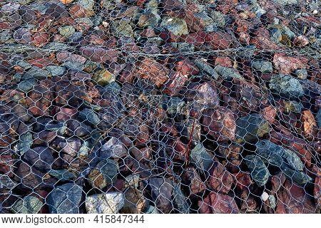 Granite Stones Under The Grate. Pattern, Background. Landslide Protection.