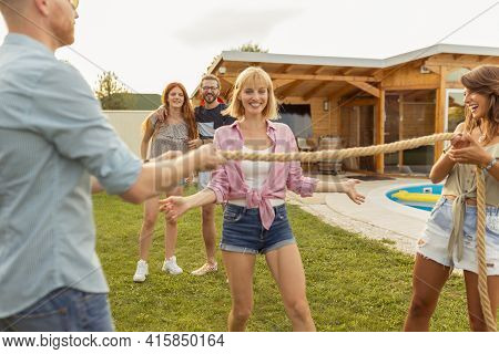 Group Of Cheerful Young Friends Having Fun At Summertime Outdoor Party By The Swimming Pool, Doing T