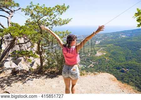 Female Tourist With Her Hands Raised Looks At Panoramic View On The Top Of The Mountain And Rejoices