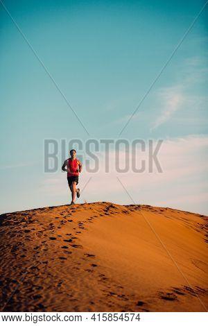 Running man athlete silhouette running across desert dune far away in sunset. Summer day warm up sport training . Vertical background.