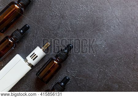 Vaping Device E-cigarette Electronic Cigarette And Liquid Bottles On Dark Black Stone Shale Backgrou