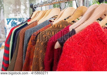 Second Hand Clothes On Hangers For Donation And Reselling. Garage Sale Or Economic Shopping Concept.