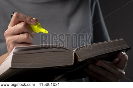 Female Student Hands Holding Yellow Highlighter And Reading Book Or Textbook, Making Notes, Underlin