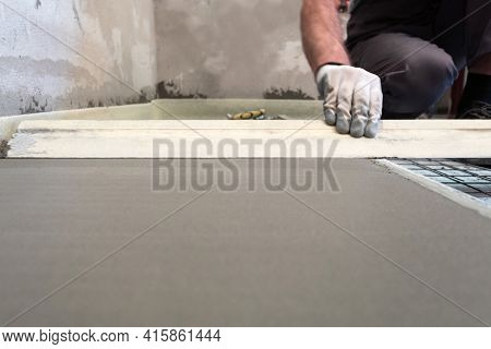 Construction Worker Performs Floor Screed Indoors. Leveling The Floor.