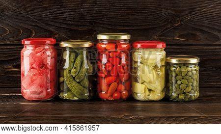 Сanned Vegetables In Glass Jars On A Dark Wooden Shelf. Preserved Artichoke In Oil, Pickled Ginger,