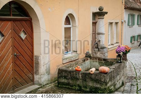 Stone Fountain, Medieval Narrow Street, Colorful Gothic And Renaissance Historical Buildings Old Tow