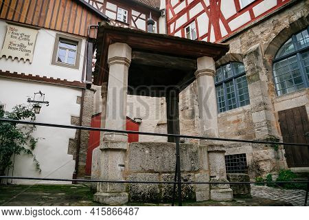 Stone Ancient Well, Medieval Narrow Street, Colorful Gothic And Renaissance Historical Buildings Old