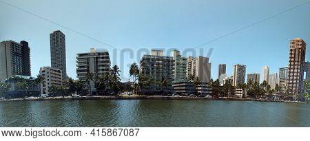 Ala Wai Canal, Hotels, Condos, And Coconut Trees On A Nice Day In Waikiki On Oahu, Hawaii.