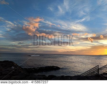 Sunset Seen From Kakaako Park Cove Over The Ocean With Clouds In Sky On Oahu, Hawaii.