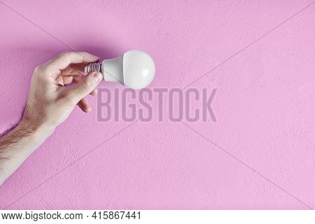 Young Adult Man's Hand Holding Energy Efficient Light Bulb Against Pink Wall Background. Concept Of