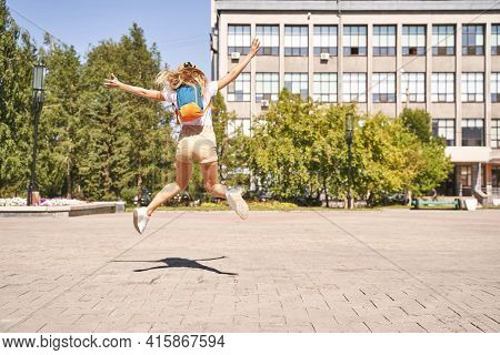 Happy Young Woman Celebrate End Of Lockdown. Borders Are Open. Jumping At Street If Town. Summer Tim