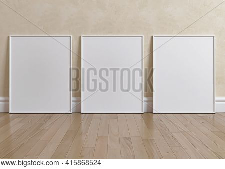 Triple 8x10 Vertical White Frame Mockup On Wooden Floor And Beige Wall. Three Empty Poster Frame Moc