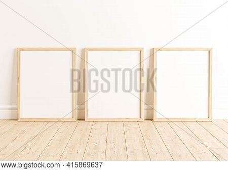 Triple 8x10 Vertical Wooden Frame Mockup On Wooden Floor And White Wall. Three Empty Poster Frame Mo