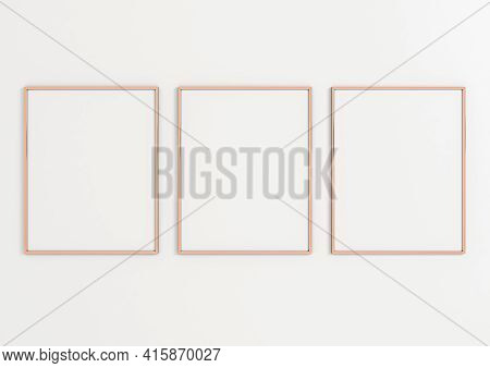 Triple 8x10 Vertical Rose Gold Frame Mockup On White Wall. Three Empty Poster Frame Mockup On White