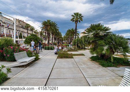 Split, Croatia - Jun 22, 2020: Splitska Riva Promenade With Palm Trees Between The Harbor And Diocle