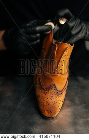 Close-up Of Shoemaker Wearing Black Latex Gloves Cleaning Old Light Brown Leather Shoes With Rag For