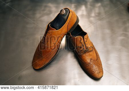 Close-up Top View Of Old Light Brown Leather Shoes With Wooden Shoe Pad To Be Repaired In Dark Craft