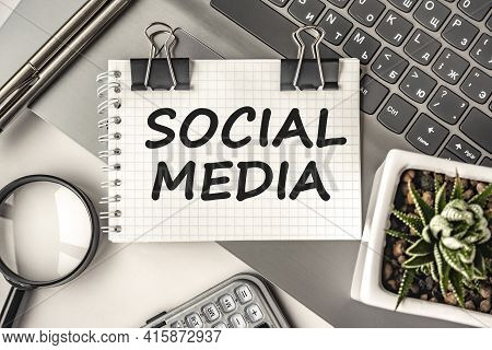 Social Media Text On A Notepad And Laptop, Office Tools. Business, Financial Concept. Remote Trainin