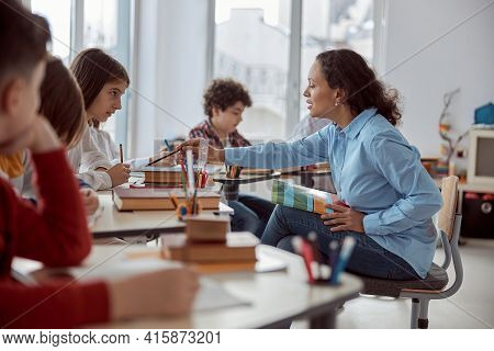 Young Teacher Helps To Read Her Student. Elementary School Kids Sitting On Desks And Reading Books I